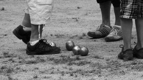 Italian ball games, feet and balls on a lawn