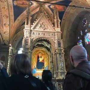 visitors in a Florentine church looking at a gothic feature