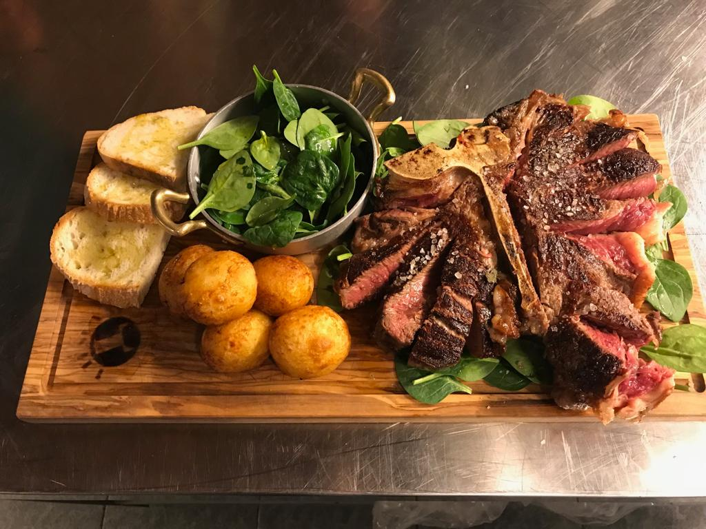 Florentine beef steak on a wooden platter with roast potatoes, bread and fresh salad